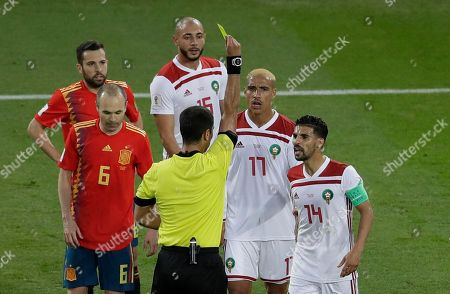 Ravshan Irmatov, Mbark Boussoufa. Referee Ravshan Irmatov from Uzbekistan shows the yellow card to Morocco's Mbark Boussoufa during the group B match between Spain and Morocco at the 2018 soccer World Cup in the Kaliningrad Stadium in Kaliningrad, Russia