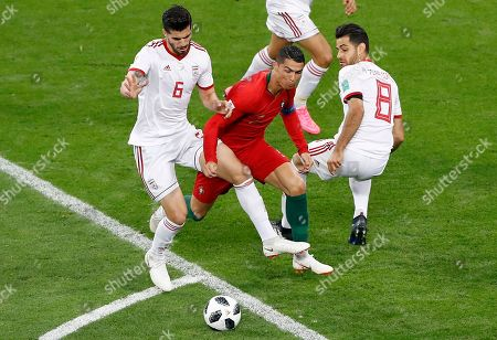 Portugal's Cristiano Ronaldo, bottom, is fouled by Iran's Saeid Ezatolahi to give away a penalty, during the group B match between Iran and Portugal at the 2018 soccer World Cup at the Mordovia Arena in Saransk, Russia