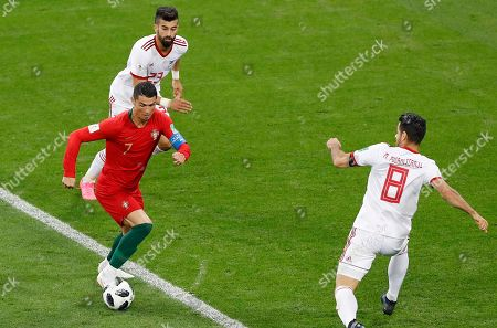 Portugal's Cristiano Ronaldo, left, dribbles past Iran's Ramin Rezaeian, top, as Iran's Morteza Pouraliganji looks him during the group B match between Iran and Portugal at the 2018 soccer World Cup at the Mordovia Arena in Saransk, Russia