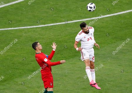 Iran's Ramin Rezaeian, right, jumps for the ball with Portugal's Cristiano Ronaldo during the group B match between Iran and Portugal at the 2018 soccer World Cup at the Mordovia Arena in Saransk, Russia