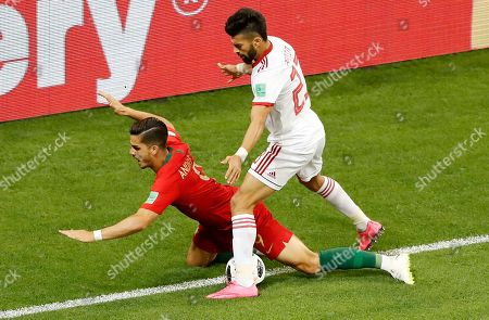 Portugal's Andre Silva, left, challenges for the ball with Iran's Ramin Rezaeian during the group B match between Iran and Portugal at the 2018 soccer World Cup at the Mordovia Arena in Saransk, Russia