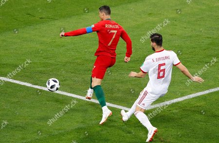 Portugal's Cristiano Ronaldo, left, dribbles past Iran's Saeid Ezatolahi during the group B match between Iran and Portugal at the 2018 soccer World Cup at the Mordovia Arena in Saransk, Russia