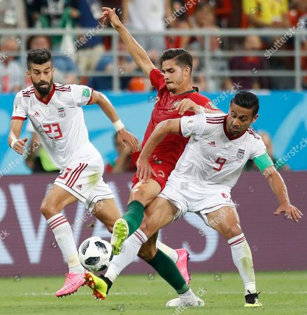 Iran's Ramin Rezaeian, left, Iran's Omid Ebrahimi, right, and Portugal's Andre Silva challenge for the ball during the group B match between Iran and Portugal at the 2018 soccer World Cup at the Mordovia Arena in Saransk, Russia