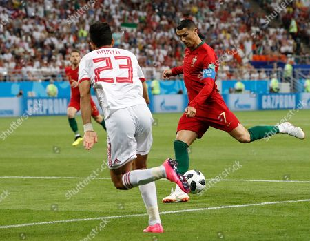 Portugal's Cristiano Ronaldo, right, kicks the ball ahead of Iran's Ramin Rezaeian during the group B match between Iran and Portugal at the 2018 soccer World Cup at the Mordovia Arena in Saransk, Russia