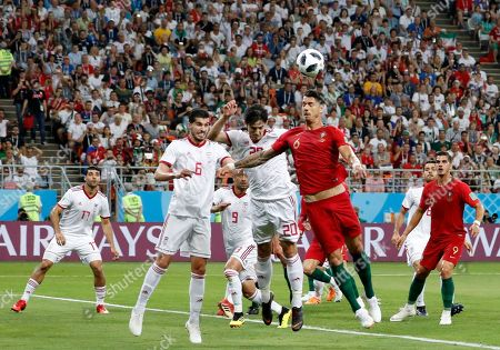 Portugal's Jose Fonte, right, jumps for the ball with Iran's Sardar Azmoun, centre, and Iran's Saeid Ezatolahi during the group B match between Iran and Portugal at the 2018 soccer World Cup at the Mordovia Arena in Saransk, Russia