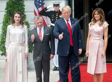 United States President Donald J. Trump, right center, gestures as he and first lady Melania Trump, right, welcome King Abdullah II bin Al-Hussein, left center, and Queen Rania, left, of the Hashemite Kingdom of Jordan to the White House in Washington, DC.