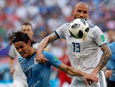Uruguay's Edinson Cavani, left, and Russia's Fyodor Kudryashov challenge for the ball during the group A match between Uruguay and Russia at the 2018 soccer World Cup at the Samara Arena in Samara, Russia