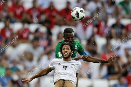 Egypt's Marwan Mohsen, front, and Saudi Arabia's Osama Hawsawi jump for the ball during the group A match between Saudi Arabia and Egypt at the 2018 soccer World Cup at the Volgograd Arena in Volgograd, Russia