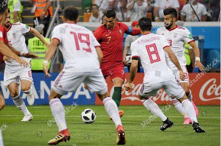 Portugal's Cristiano Ronaldo (center) with Iran's Majid Hosseini (left) and Morteza Pouraliganji (right) during the match
