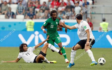 Saudi Arabia's Yasir Alshahrani, center, duels for the ball with Egypt's Mohamed Elneny, left, and Ahmed Fathi during the group A match between Saudi Arabia and Egypt at the 2018 soccer World Cup at the Volgograd Arena in Volgograd, Russia