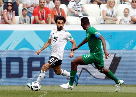 Egypt's Mohamed Salah, left, duels for the ball with Saudi Arabia's Osama Hawsawi during the group A match between Saudi Arabia and Egypt at the 2018 soccer World Cup at the Volgograd Arena in Volgograd, Russia