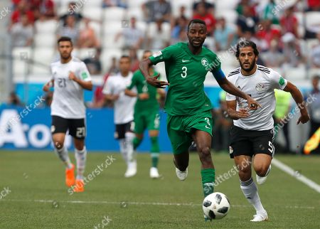 Saudi Arabia's Osama Hawsawi, center, and Egypt's Marwan Mohsen run for the ball during the group A match between Saudi Arabia and Egypt at the 2018 soccer World Cup at the Volgograd Arena in Volgograd, Russia