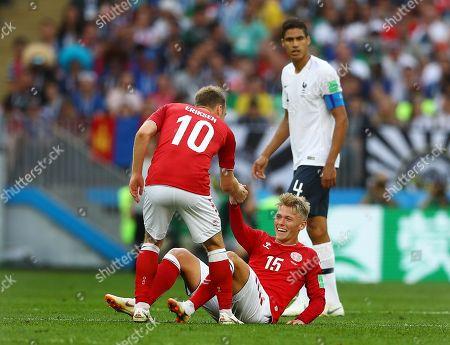 Christian Eriksen of Denmark helps up Viktor Fischer