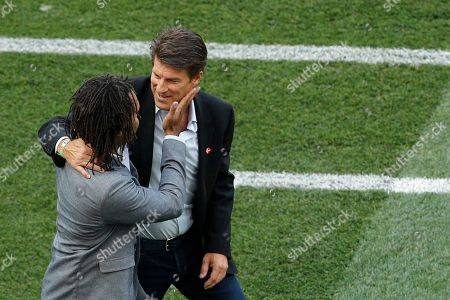 Denmark soccer legend Michael Laudrup, right, embraces France's former soccer player Christian Karembeu prior to the start of the group C match between Denmark and France at the 2018 soccer World Cup at the Luzhniki Stadium in Moscow, Russia