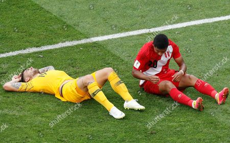 Australia's Joshua Risdon, left, and Peru's Edison Flores are lying on the pitch during the group C match between Australia and Peru, at the 2018 soccer World Cup in the Fisht Stadium in Sochi, Russia