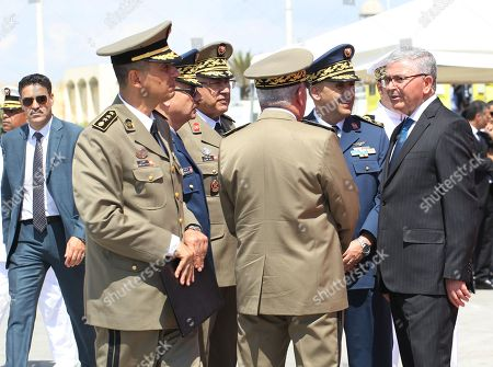 Tunisian Minister of Defence Abdelkarim Zbidi (R) greets military officers while attending the Tunisian naval forces military intervention drill