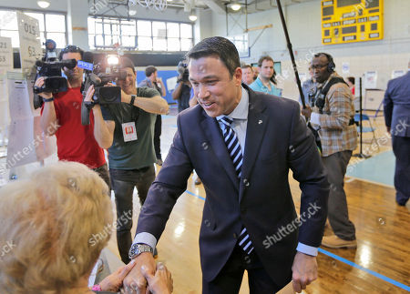 Former U.S. Rep. Michael Grimm talks with a woman at his polling site in the Staten Island borough of New York, . New York City's only Republican congressman, U.S. Rep. Daniel Donovan, will try to hold off a fierce challenge in the state's primary election Tuesday from former U.S. Rep. Michael Grimm, who is trying to make a political comeback after serving prison time for tax fraud