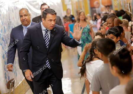 Former U.S. Rep. Michael Grimm looks for a high-five from kids after voting at his polling site in a school in the Staten Island borough of New York, . New York City's only Republican congressman, U.S. Rep. Daniel Donovan, will try to hold off a fierce challenge in the state's primary election Tuesday from Grimm, who is trying to make a political comeback after serving prison time for tax fraud