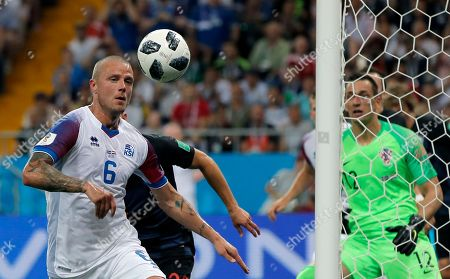 Iceland's Ragnar Sigurdsson, left, duels for the ball with Croatia's Josip Pivaric during the group D match between Iceland and Croatia, at the 2018 soccer World Cup in the Rostov Arena in Rostov-on-Don, Russia