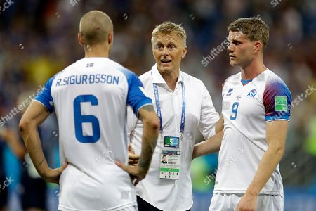 From left, Iceland's Ragnar Sigurdsson, coach Heimar Hallgrimsson and Bjorn Sigurdarson stand on the pitch at the end of the group D match between Iceland and Croatia, at the 2018 soccer World Cup in the Rostov Arena in Rostov-on-Don, Russia, . Croatia won 2-1