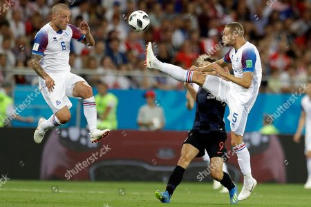 Iceland's Ragnar Sigurdsson, left, and Iceland's Sverrir Ingason jump for the ball during the group D match between Iceland and Croatia, at the 2018 soccer World Cup in the Rostov Arena in Rostov-on-Don, Russia