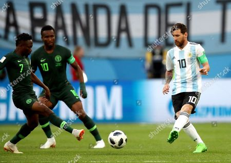 Lionel Messi of Argentina passes past Ahmed Musa of Nigeria and Mikel John Obi