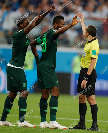 Referee Cuneyt Cakir gestures to Nigeria's John Obi Mikel, center and Odion Ighalo during the group D match between Argentina and Nigeria, at the 2018 soccer World Cup in the St. Petersburg Stadium in St. Petersburg, Russia