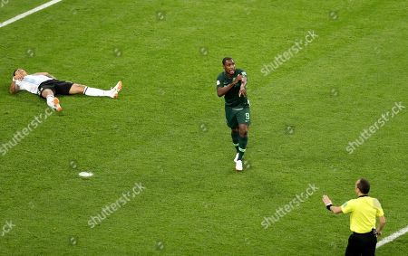 Nigeria's Odion Ighalo gestures to Referee Cuneyt Cakir, right, after the ball hit the arm of Argentina's Marcos Rojo, left, in the box during the group D match between Argentina and Nigeria, at the 2018 soccer World Cup in the St. Petersburg Stadium in St. Petersburg, Russia