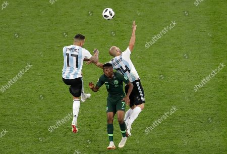 Argentina's Nicolas Otamendi and Javier Mascherano, right, jump for the ball with with Nigeria's Ahmed Musa during the group D match between Argentina and Nigeria, at the 2018 soccer World Cup in the St. Petersburg Stadium in St. Petersburg, Russia