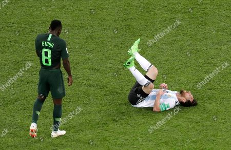 Argentina's Lionel Messi lies down on the pitch in front of Nigeria's Odion Ighalo at the end of the group D match between Argentina and Nigeria, at the 2018 soccer World Cup in the St. Petersburg Stadium in St. Petersburg, Russia