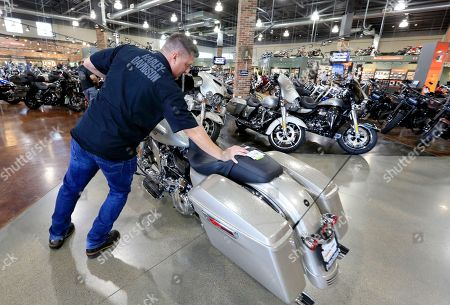 Jason Davis, an employee at the Dillon Brothers Harley Davidson dealership, moves a Street Glide Harley Davidson motorcycle which was sold, at in Omaha, Neb