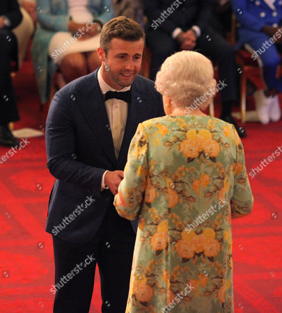 Mr. Hunter Johnson from Australia receives his Young Leaders Award from Queen Elizabeth II during a ceremony in the Ballroom at Buckingham Palace.