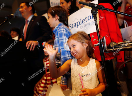 Walker Stapleton, Olivia Stapleton. Four-year-old Olivia Stapleton, front, waves as her father, Walker, back, speaks after he won the Republican nomination to run for Colorado's governorship during an election night watch party in a hotel, in Greenwood Village, Colo. Stapleton secured the nomination Tuesday against businessmen Victor Mitchell, Doug Robinson and Greg Lopez