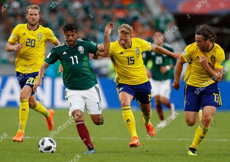 Carlos Vela, Oscar Hiljemark. Mexico's Carlos Vela, center left, and Sweden's Oscar Hiljemark, center right, challenge for the ball during the group F match between Mexico and Sweden, at the 2018 soccer World Cup in the Yekaterinburg Arena in Yekaterinburg, Russia