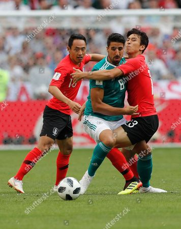 South Korea's Koo Ja-cheol, right, and South Korea's Moon Seon-min, left, vie for the ball with Germany's Sami Khedira, centre, during the group F match between South Korea and Germany, at the 2018 soccer World Cup in the Kazan Arena in Kazan, Russia