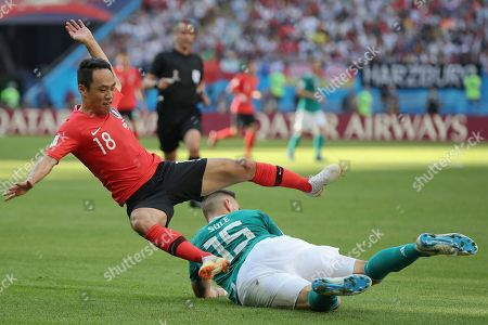 South Korea's Moon Seon-min, left, and Germany's Niklas Suele fight for the ball during the group F match between South Korea and Germany, at the 2018 soccer World Cup in the Kazan Arena in Kazan, Russia