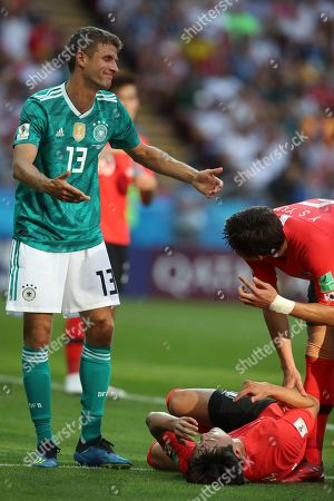 Stock Photo of Germany's Thomas Mueller, left, talks with South Korea's Kim Young-gwon, on the ground, and South Korea's Yun Young-sun during the group F match between South Korea and Germany, at the 2018 soccer World Cup in the Kazan Arena in Kazan, Russia