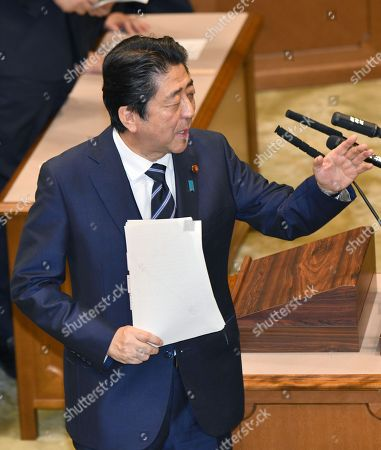 Japan Prime Minister Shinzo Abe answers former Foreign Minister Katsuya Okada, now an independent lawmaker