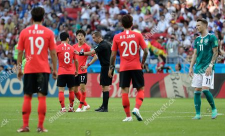Referee Mark Geiger from the US talks to South Korea's Ju Se-jong, 2nd left, during the group F match between South Korea and Germany, at the 2018 soccer World Cup in the Kazan Arena in Kazan, Russia