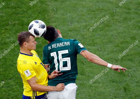 Sweden's John Guidetti, left, jumps for the ball with Mexico's Hector Herrera during the group F match between Mexico and Sweden, at the 2018 soccer World Cup in the Yekaterinburg Arena in Yekaterinburg, Russia