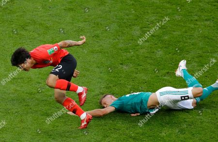 Germany's Joshua Kimmich falls in a clash with South Korea's Go Yo-han during the group F match between South Korea and Germany, at the 2018 soccer World Cup in the Kazan Arena in Kazan, Russia