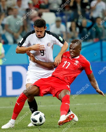 Stock Image of Denis Zakaria (R) of Switzerland and Daniel Colindres of Costa Rica in action during the FIFA World Cup 2018 group E preliminary round soccer match between Switzerland and Costa Rica in Nizhny Novgorod, Russia, 27 June 2018. (RESTRICTIONS APPLY: Editorial Use Only, not used in association with any commercial entity - Images must not be used in any form of alert service or push service of any kind including via mobile alert services, downloads to mobile devices or MMS messaging - Images must appear as still images and must not emulate match action video footage - No alteration is made to, and no text or image is superimposed over, any published image which: (a) intentionally obscures or removes a sponsor identification image; or (b) adds or overlays the commercial identification of any third party which is not officially associated with the FIFA World Cup)