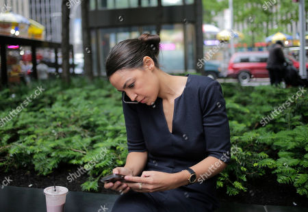 "Alexandria Ocasio-Cortez does a phone interview while sitting near Rockefeller Center in New York, . The 28-year-old political newcomer who upset U.S. Rep. Joe Crowley in New York's Democrat primary says she brings an ""urgency"" to the fight for working families"