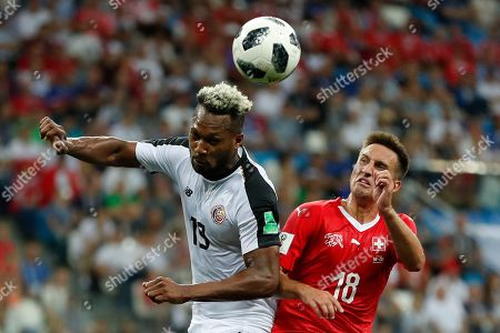 Costa Rica's Rodney Wallace, left, and Switzerland's Mario Gavranovic jump for the ball during the group E match between Switzerland and Costa Rica, at the 2018 soccer World Cup in the Nizhny Novgorod Stadium in Nizhny Novgorod, Russia