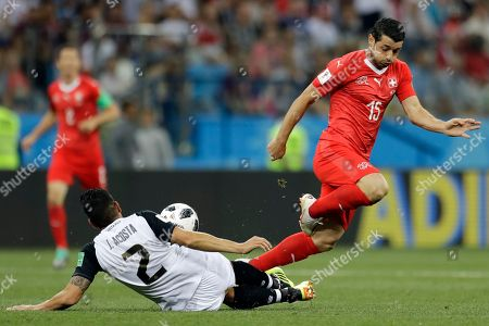 Stock Photo of Costa Rica's Johnny Acosta, left, and Switzerland's Blerim Dzemaili fight for the ball during the group E match between Switzerland and Costa Rica, at the 2018 soccer World Cup in the Nizhny Novgorod Stadium in Nizhny Novgorod, Russia