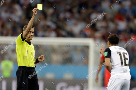 Referee Clement Turpin from France, left, gives Costa Rica's Cristian Gamboa a yellow card during the group E match between Switzerland and Costa Rica, at the 2018 soccer World Cup in the Nizhny Novgorod Stadium in Nizhny Novgorod, Russia