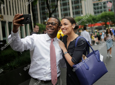 "Alexandria Ocasio-Cortez takes a selfie with a pedestrian that congratulated her near Rockefeller Center in New York, . The 28-year-old political newcomer who upset U.S. Rep. Joe Crowley in New York's Democrat primary says she brings an ""urgency"" to the fight for working families"