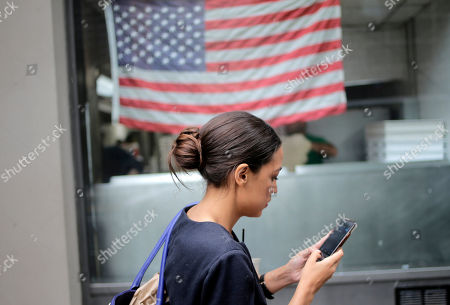 "Alexandria Ocasio-Cortez checks her phone while walking to her next appointment in New York, . The 28-year-old political newcomer who upset U.S. Rep. Joe Crowley in New York's Democrat primary says she brings an ""urgency"" to the fight for working families"