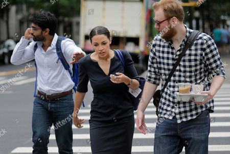 "Alexandria Ocasio-Cortez is escorted between interviews by men who worked on her campaign in New York, . The 28-year-old political newcomer who upset U.S. Rep. Joe Crowley in New York's Democrat primary says she brings an ""urgency"" to the fight for working families"