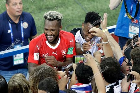 Costa Rica's Kendall Waston and Rodney Wallace, right, meet family and friends at the end of the group E match between Switzerland and Costa Rica, at the 2018 soccer World Cup in the Nizhny Novgorod Stadium in Nizhny Novgorod, Russia